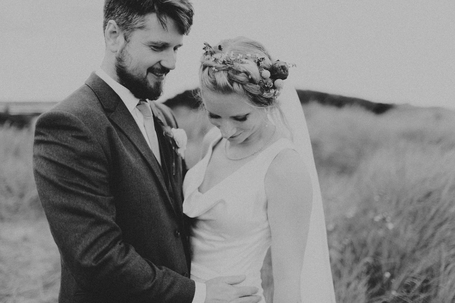 black and white image of bride and groom in dunes